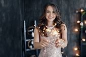 Girl With A Sparkler Near The Christmas Tree. A Cheerful Young Woman With A Cute Smile In A Beige Dr poster