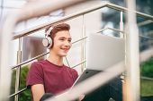 Smiling teenage boy with a laptop on the street. Handsome young man works on a notebook, outdoors. C poster