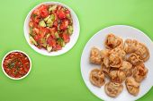 Dumplings On A White Plate Against A Lime Background. Dumplings Meat In Tomato Sauce With Vegetable  poster