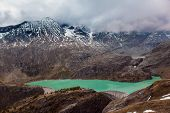 Green water of alpine lake. The first snow fell on Grossglockner Alpine Road. Austria. Ecological, a poster