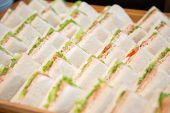 Close Up Of Many Sandwiches On Wooden Tray poster