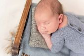 Funny newborn sleeping comfortably on tiny bed poster