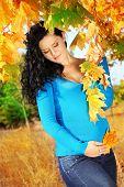 Mulher bonita grávida em folhas de outono ao ar livre, ao ar livre