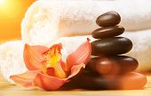 Spa background. White towels on exotic plant, beautiful orchid flower and balancing stones for relax poster