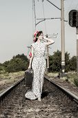 Young Girl With Old Suitcase On The Railway Tracks. A Pretty Girl Is Walking With A Suitcase. A Teen poster