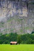 Small Barn Close To A Steep Rocky Mountain In Switzerland
