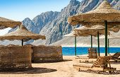 Beach Umbrellas And Wooden Lounge Chairs On The Sand Of The Beach Against The Backdrop Of The Sea An poster