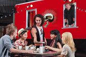 stock photo of food truck  - Handsome man bringing plate of food to group of diners at food truck - JPG