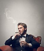 handsome boss smokes cigar sitting on a red armchair