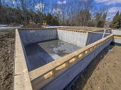 stock photo of foundation  - Poured concrete basement and house foundation to a new house - JPG