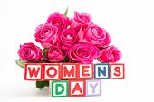 Bunch of pink roses next to wooden blocks spelling womens day on white background