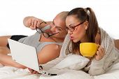 Young couple lying on bed and watching laptop