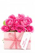Bouquet of beautiful pink roses next to a pink gift with a happy mothers day card on white backgroun
