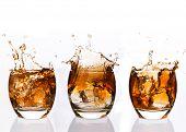 Serial arrangement of whiskey splashing in tumbler on white background