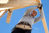 stock photo of carpentry  - carpenter at work with wooden  roof construction - JPG