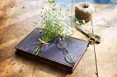 Vintage book, vintage eyeglasses and small bouquet of baby's breath flowers on old worn desk, in war