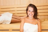 Young beautiful woman having a sauna bath in a steam room