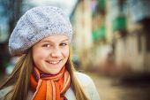 stock photo of beret  - Teen Girl Wearing White Beret And Orange Scarf In Windy Day - JPG