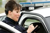 image of lightbar  - a female police officer writes a ticket while standing next to her patrol car - JPG