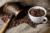 Cezve And Cup With Freshly Roasted Coffee Beans On Sackcloth