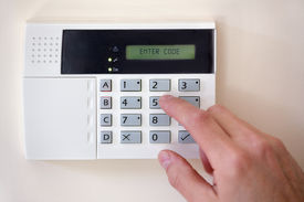 foto of keypad  - Security alarm keypad with person arming the system - JPG