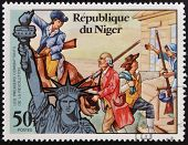 NIGER - CIRCA 1976: stamp shows Statue of Liberty and the first fighters of the Revolution