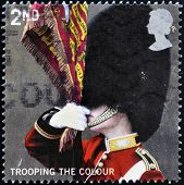 A stamp printed in Great Britain shows Ensign of the Scots Guards trooping the colour