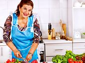 Mature woman preparing dinner at kitchen.