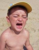 Crying Little Boy On The Beach