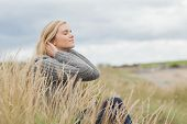 Side view of a cute thoughtful young woman sitting on grass at beach