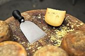 Special knife and famous italian cheese pecorino on small wooden table.