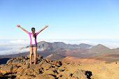 Hiking woman on top happy and celebrating success. Female hiker on top of the world cheering in winning gesture having reached summit of mountain, East Maui Volcano, Haleakala national park Hawaii.