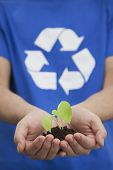 Close-up of young man holding seedling in his hands with recycling symbol on his t-shirt