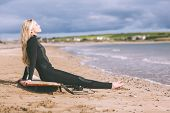 Side view of a beautiful blond in wet suit with surfboard at the beach