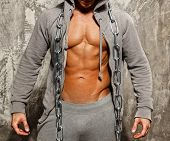 Sporty muscular man in grey hoodie with heavy metal chain