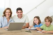 Portrait of happy parents with laptop while children coloring at table in house