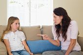 Young mother scolding girl while sitting on sofa at home
