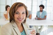 Close-up of a smiling businesswoman having coffee with colleagues in meeting in background at the of