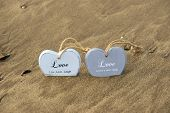 picture of quicksand  - two inscribed wooden love hearts sinking in the quicksand on a wild Atlantic way Irish beach in summer - JPG