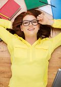 education and home concept - smiling redhead female student touching eyeglasses and lying on floor