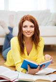 education and home concept - smiling student girl reading books at home