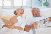 Cheerful mature couple with newspaper and book lying in bed at home