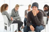 Upset man in rehab group looking at camera at therapy session