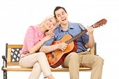 Young guy playing guitar to his girlfriend seated on bench isolated on white background