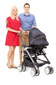 Young parents with a baby stroller posing isolated on white background
