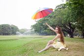 Woman With Umbrella And Sitting On The Lawn.