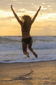 Happy young woman girl in bikini jumping on a beach at sunset or sunrise