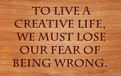To live a creative life, we must lose our fear of being wrong - quote by unknown author on wooden r