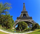 Huge and beautiful Eiffel Tower. At the foot of the tower is designed park with paths and pond. The