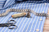 Closeup of a blue striped mens dress shirt ready for tailoring with scissors, thread, needle thimble